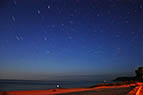 Time exposure of stars above a Lake Michigan beach.